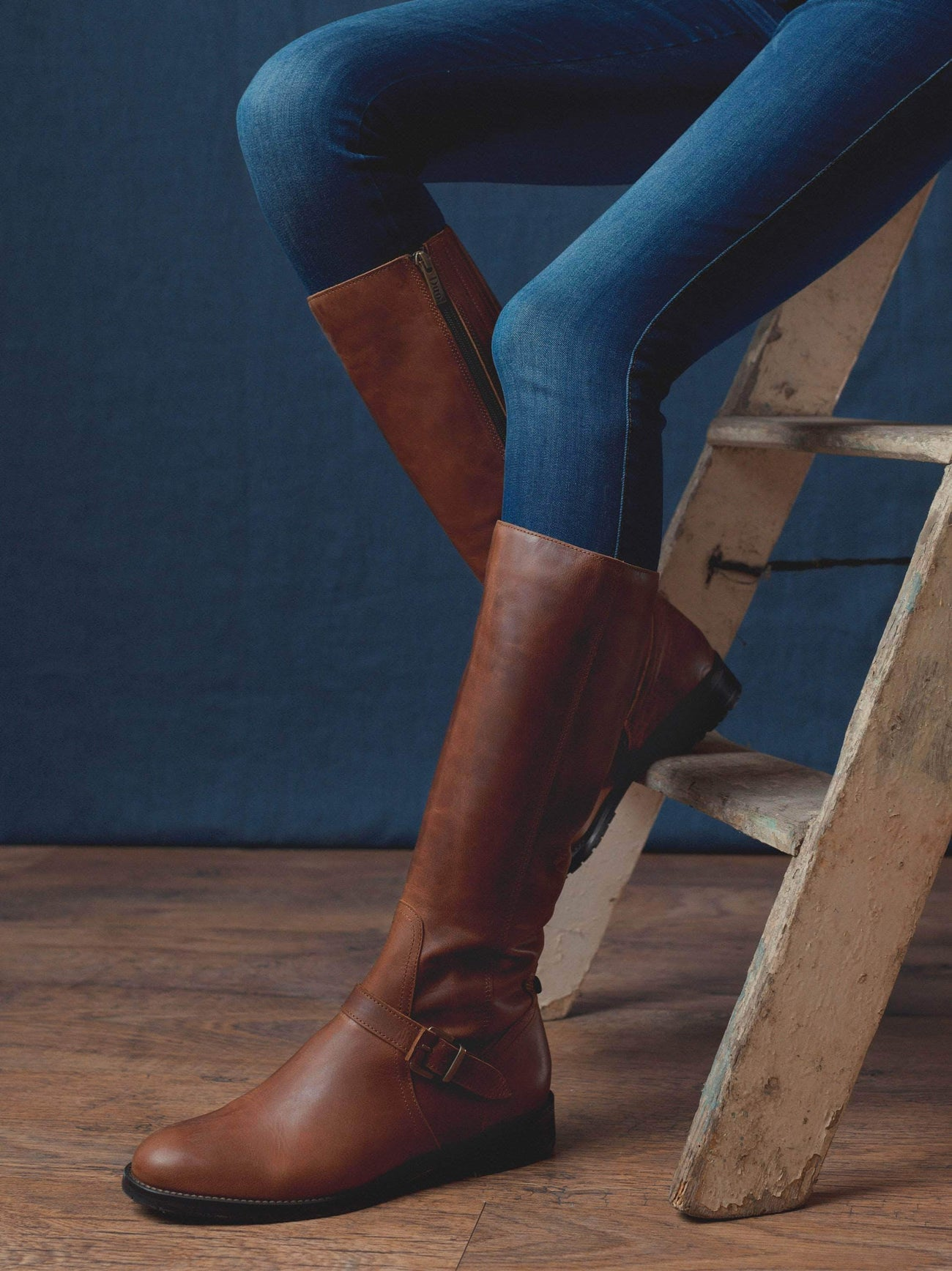 Sherwoord, a knee high boot with detailed with a brown buckled strap over the neatly cut ankle.