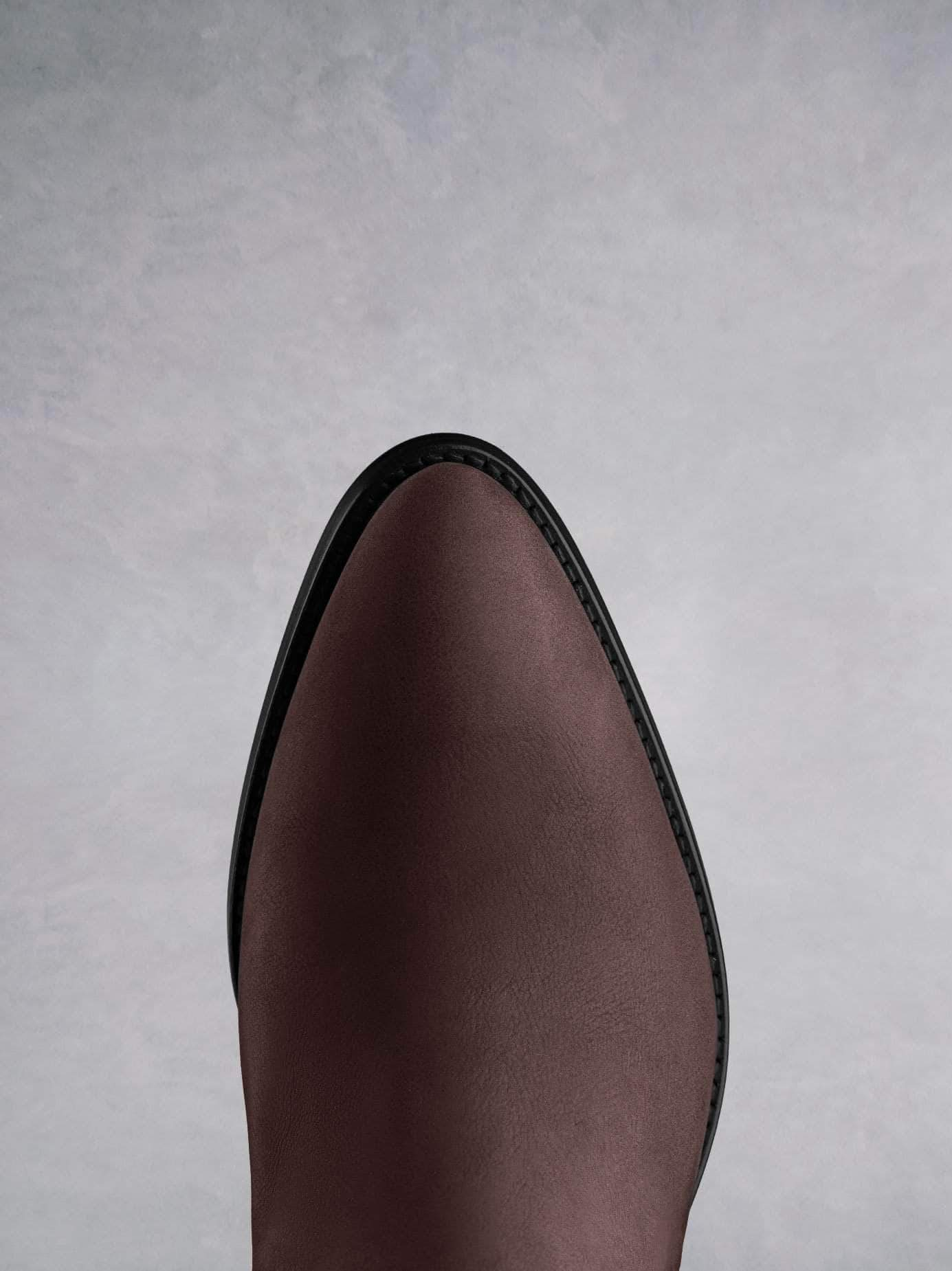This burgundy ankle boot features a western style pointed toe shape.