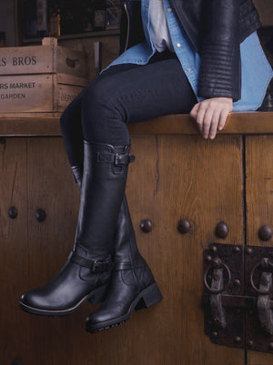 The Demeter; a knee high textured black leather biker boot with buckles.