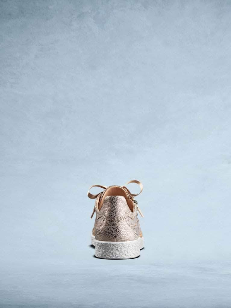 This stylish rose gold trainer has a contrasting textured white sole.