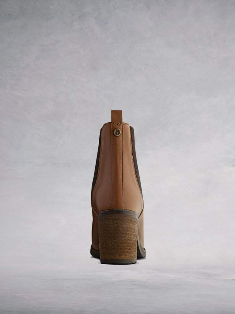 With a stacked leather veneer around a block heel with a contrasting brown rubber sole.