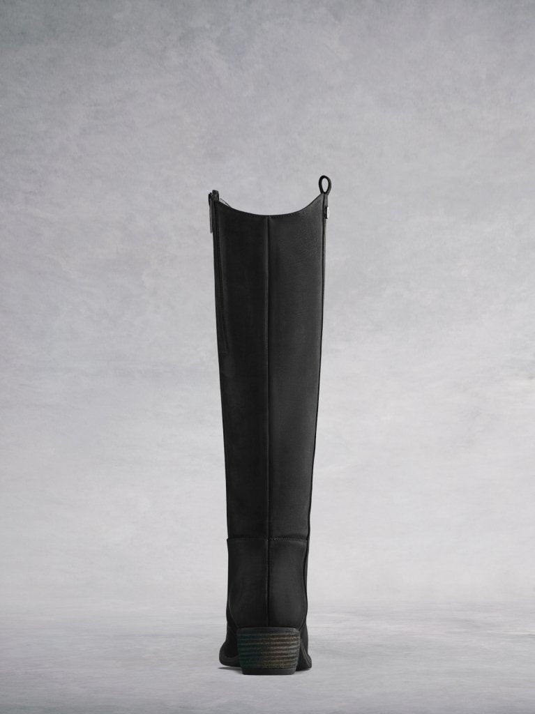 Staple boot with a curved topline and a low stacked leather veneer heel.
