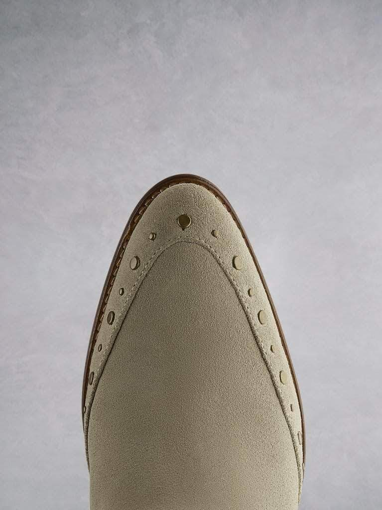 Emilia in taupe suede, featuring stud detailing that highlights the almond toe shape.