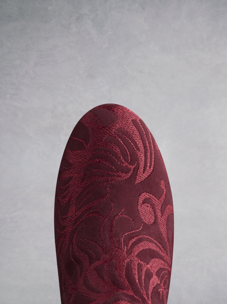 The round burgundy suede toe is covered in tonal embroidery.
