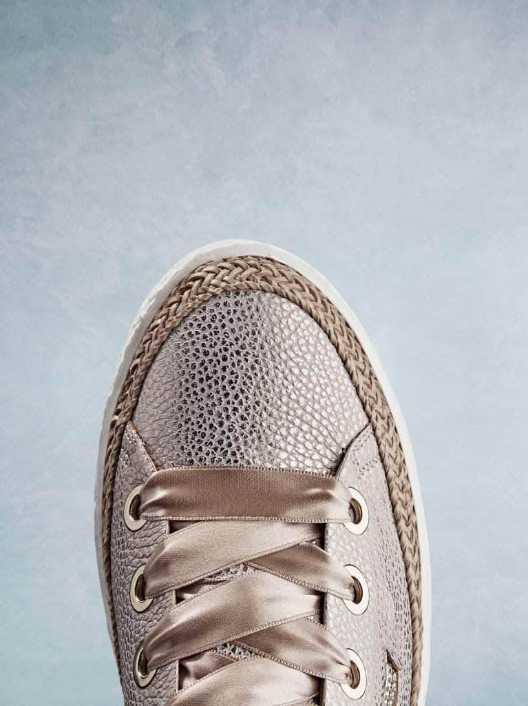 This rose gold trainer has a smooth round toe highlighted by the lace trim.