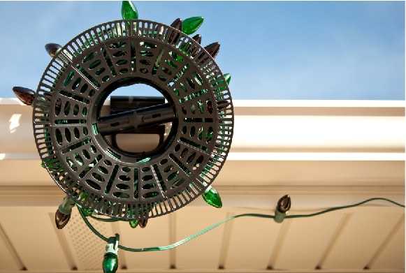 Install N Store Light storage reel hanging on rain gutter during Christmas light installation