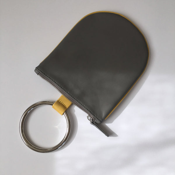 "Ring pouch from Myers Collective's collaboration with Otaat. Cowhide leather pouch, with 3"" ring that slips easily on the wrist. Unlined. Smoke (grey) body / Yellow trim, nickel ring."