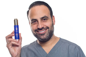 Dr. Ben Talei smiling and presenting AuraSilk bottle held in his hand