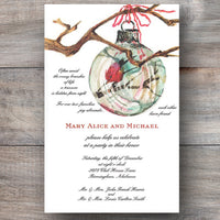 Christmas invitation with red cardinal inside hanging ornament