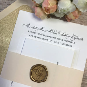 Close up of blush and gold letterpress wedding invitations
