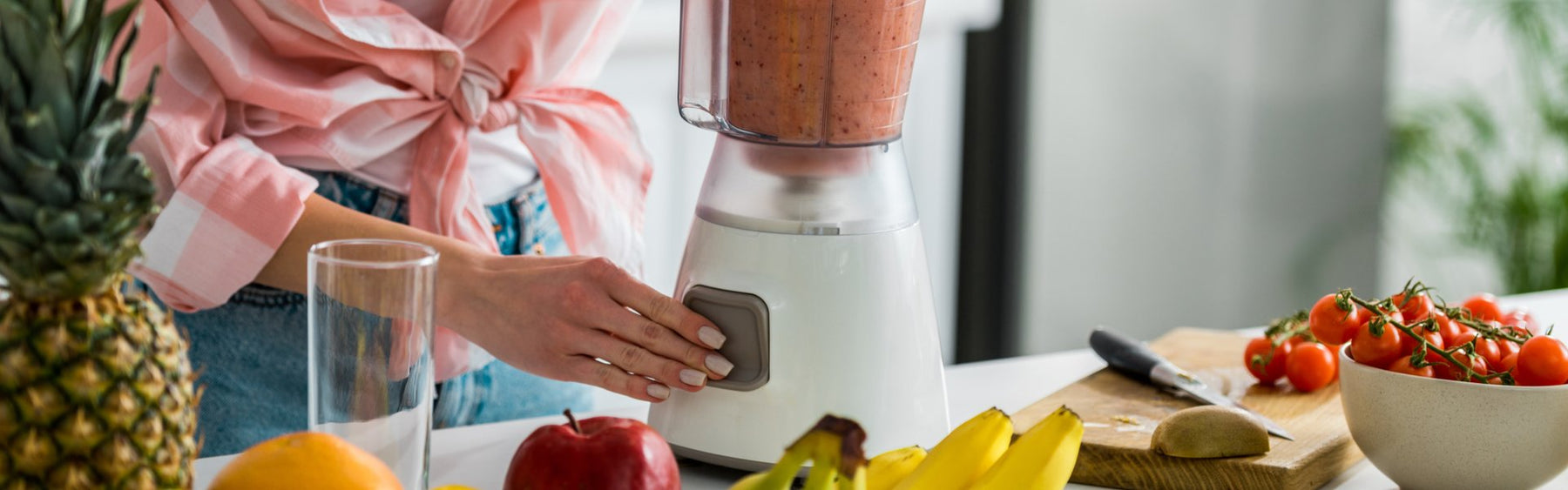 Woman making a smoothie in a blender from fruits and vegetables