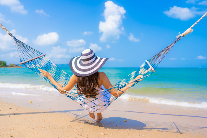 Woman with long hair relaxing in a hammock on the beach