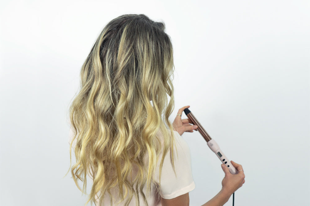 Woman holding a ceramic and titanium curling wand