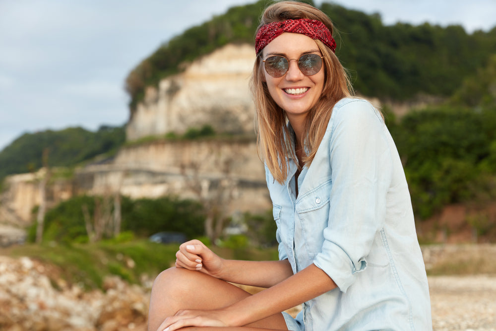 woman in nature wearing a red bandana and sunglasses