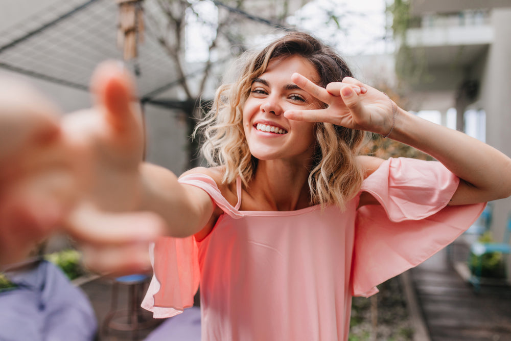 Woman taking a selfie as she waves the peace sign with her hands.