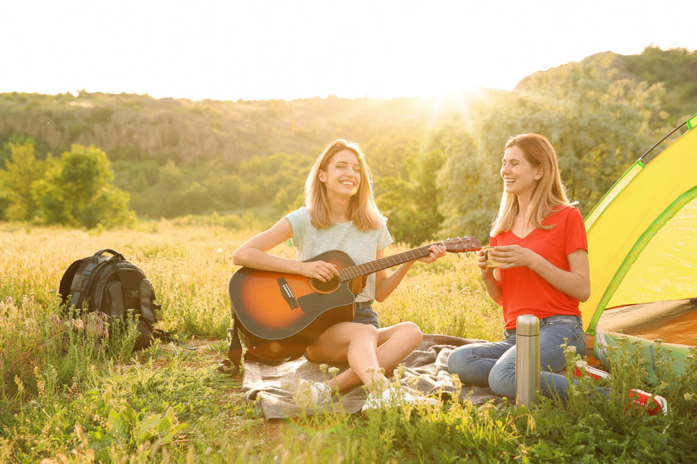 Woman camping and singing songs on a guitar