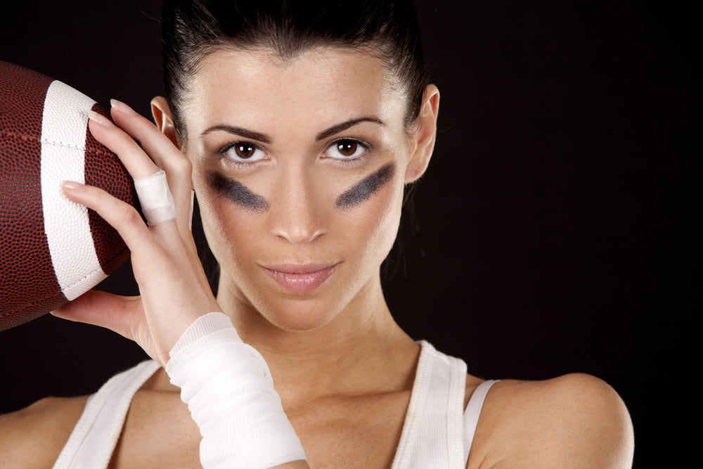 Woman holding a football with a bandaid on her ring finger and black stripes under her eyes