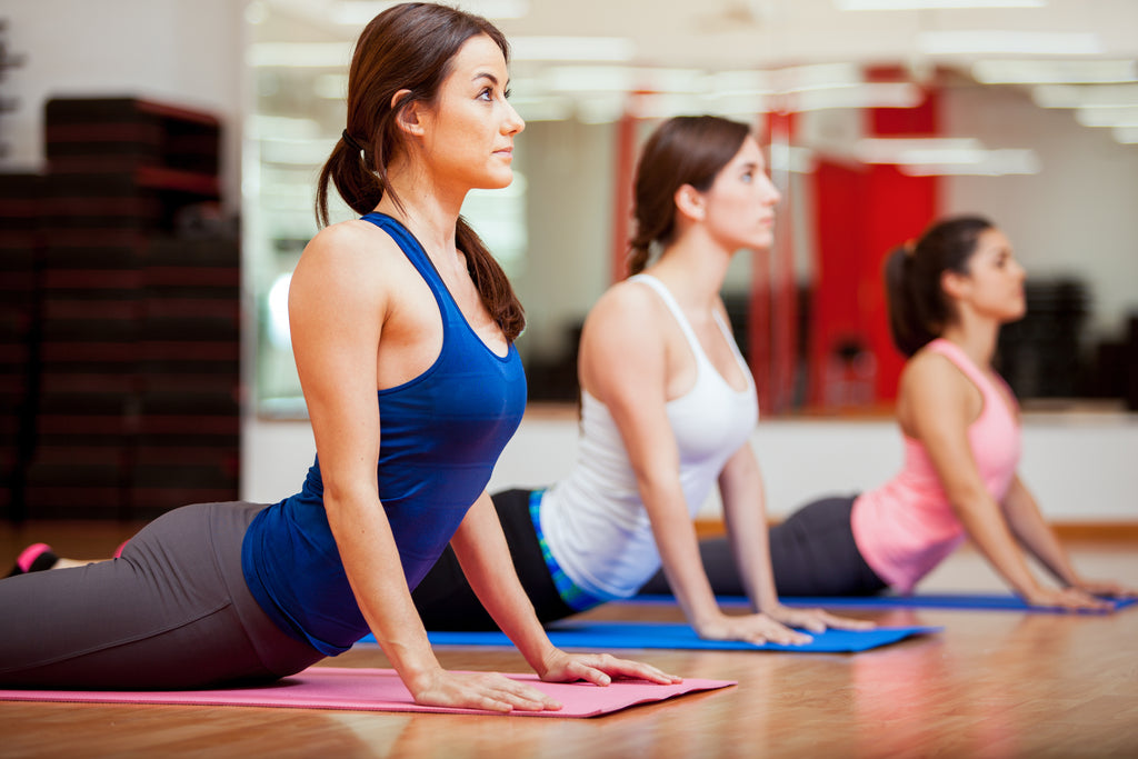 3 Woman doing the upward Dog yoga pose as they slowly go out of focus