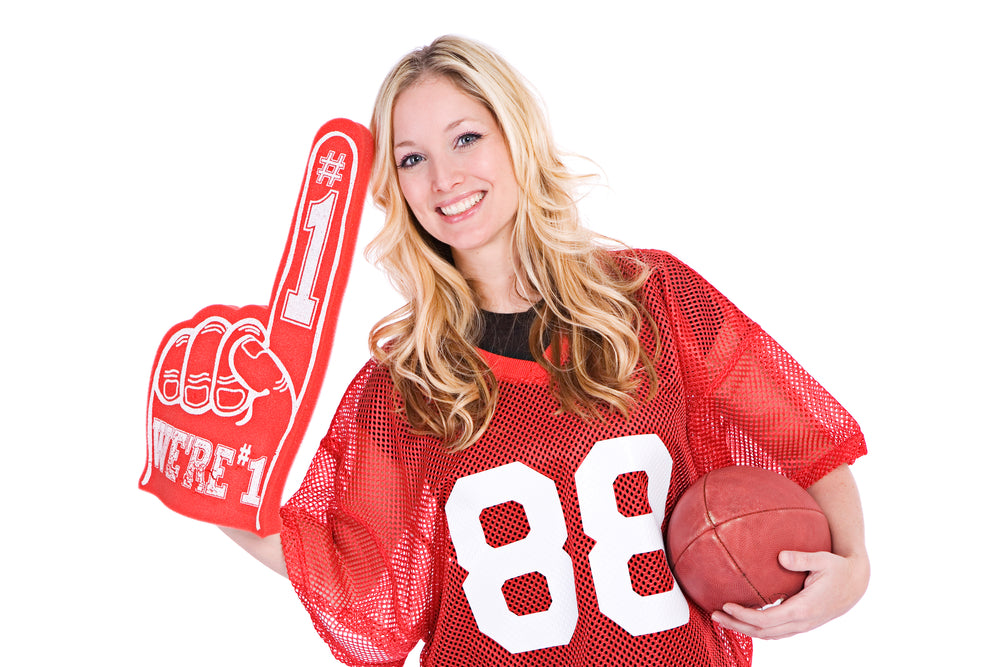 Woman holding a football and holding a red 1 foam finger