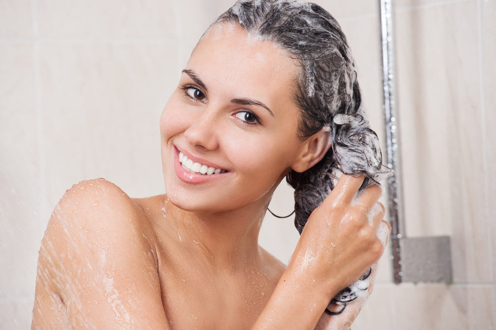 Woman washing her hair in the shower while smiling