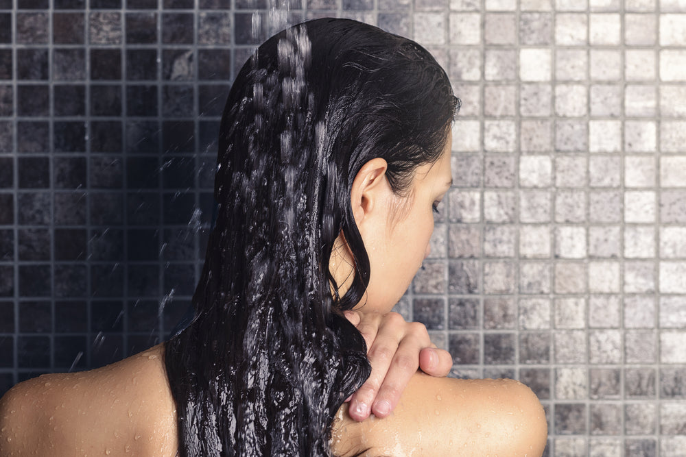 woman rinsing hair in the shower