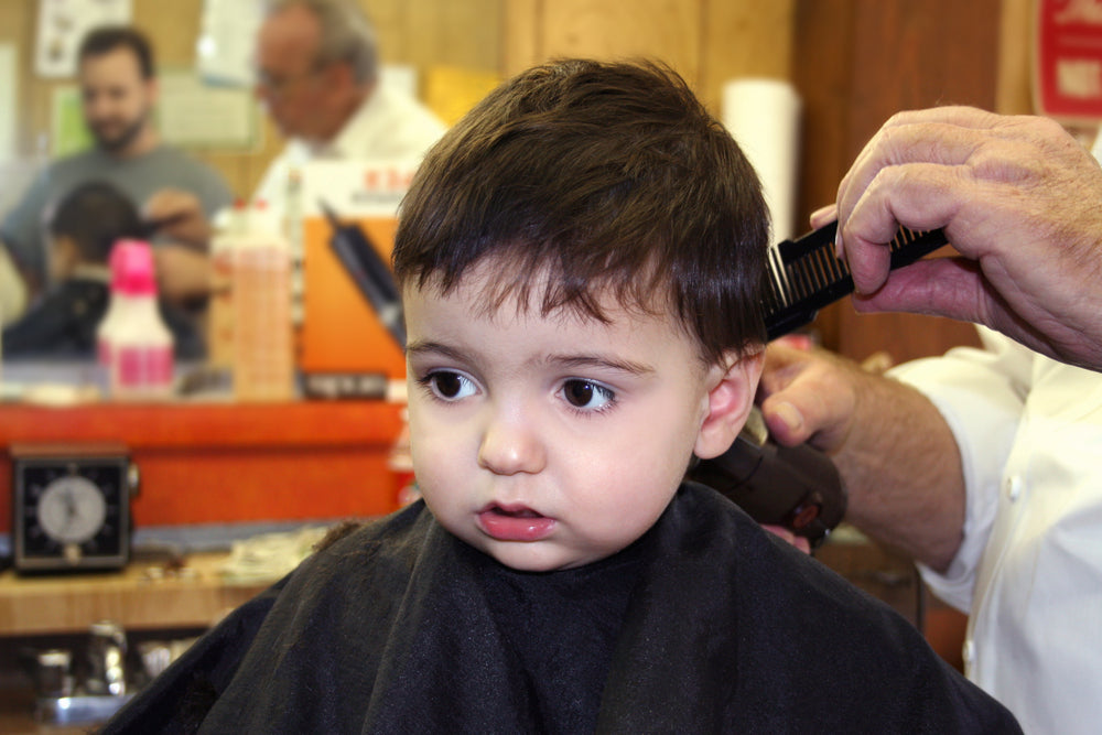 Child looking in mirror as he gets a haircut