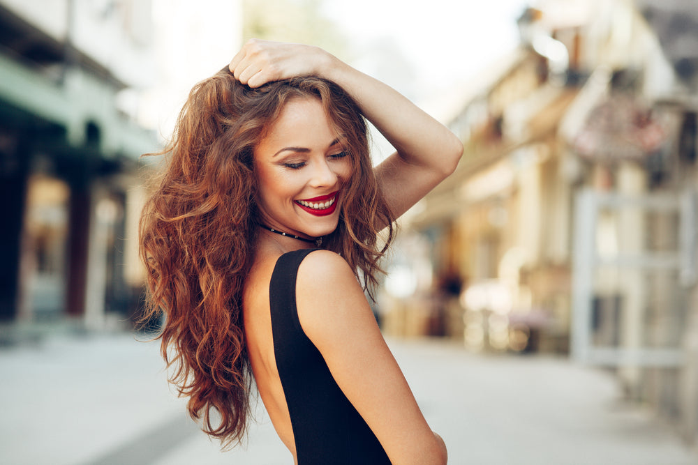 Red head woman with curyly hair smiling