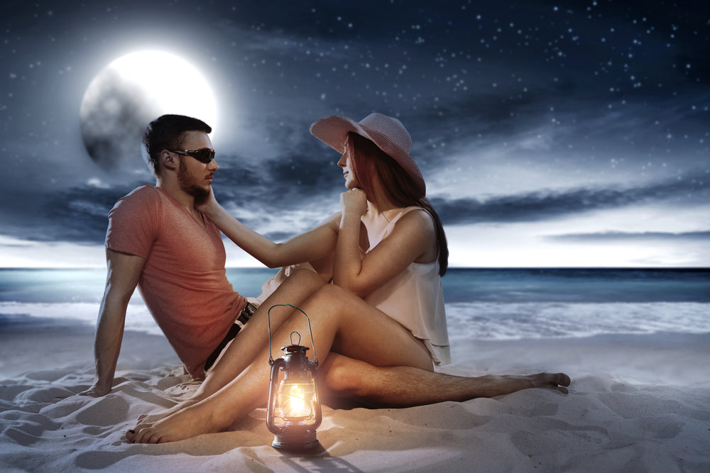Man and woman sitting in the sand of the beach under the light of a full moon