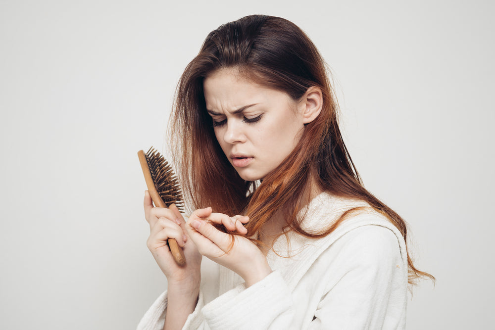 woman looking at her hair brush.