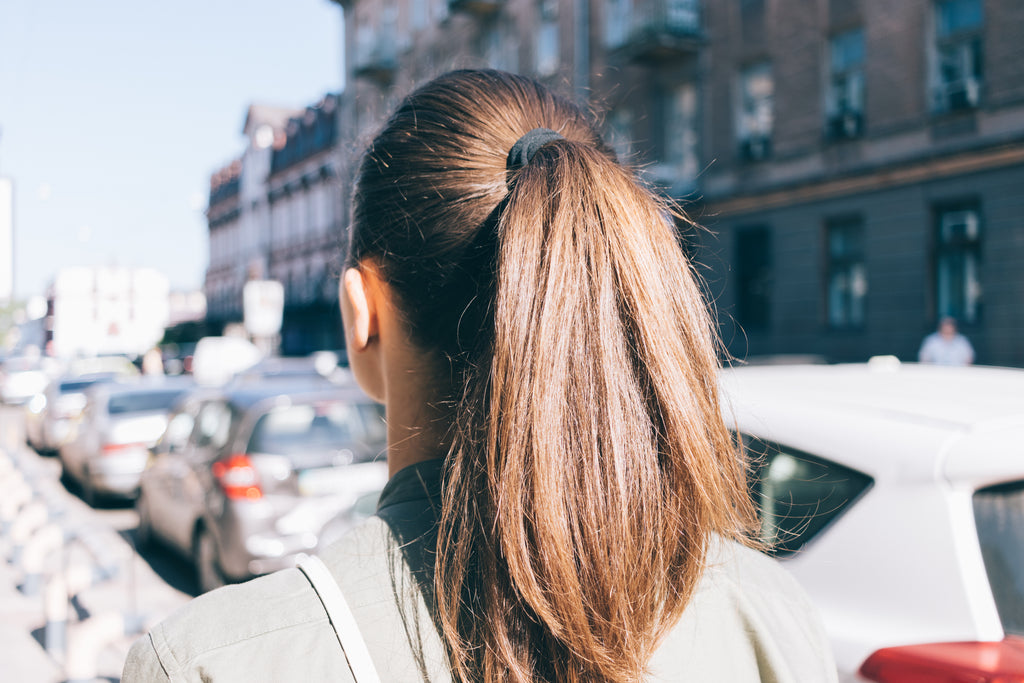 Girl in a ponytail walking down a street