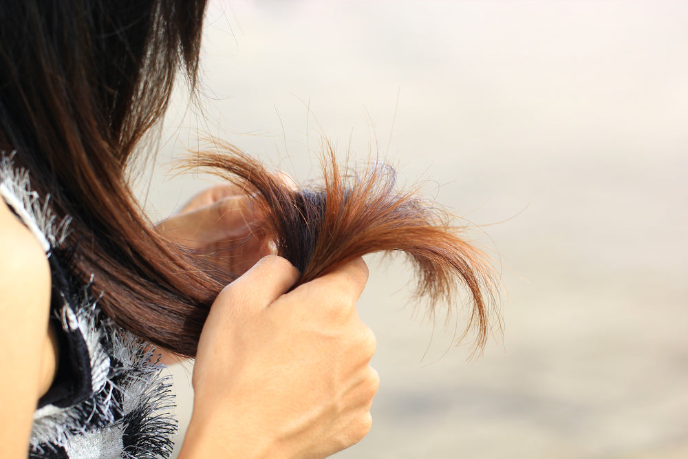 Woman holding the ends of her hair looking for split ends