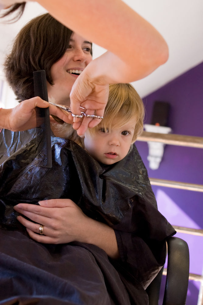 Blond child getting first haircut.