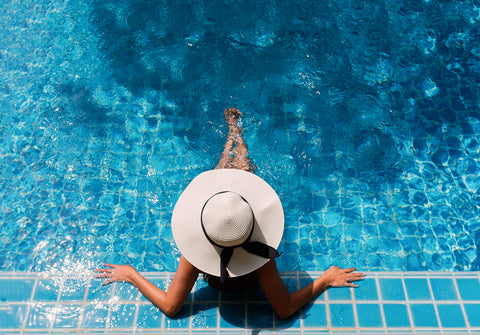 woman wearing sun hat in swimming pool