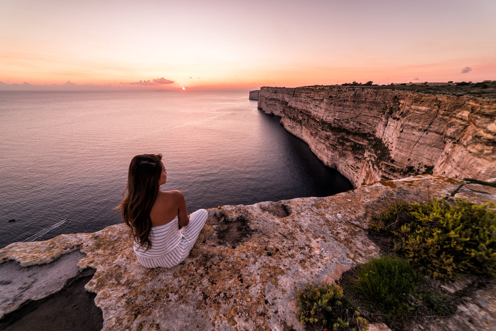 woman looking at sunset as she sits at the edge of a cliff