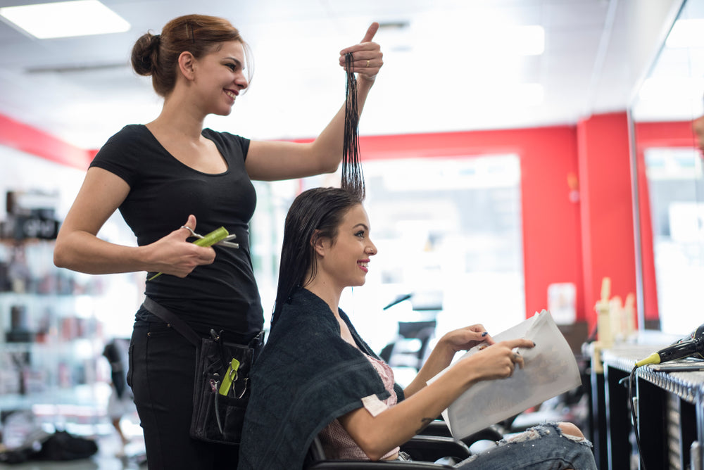 hair stylist talking to her client about the length of hair to cut