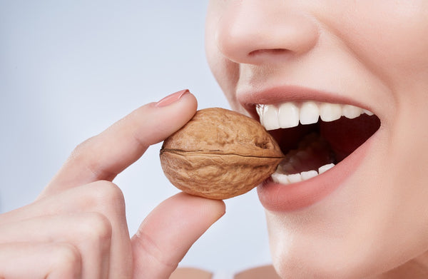 Woman biting on walnut