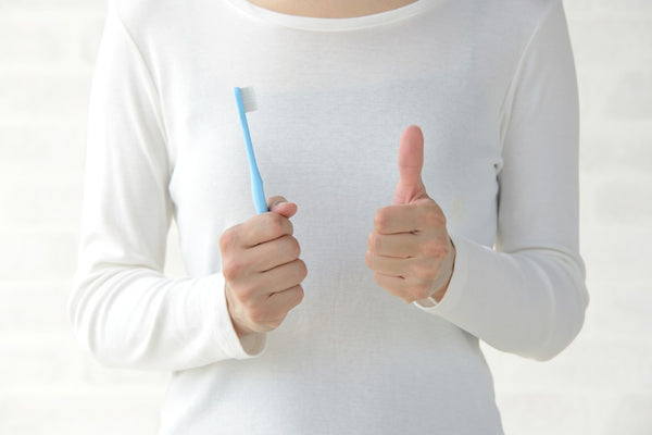Women holding toothbrush thumbs up