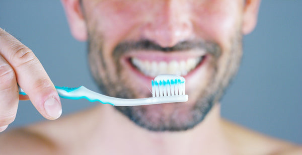 Man brushing teeth with fluoride toothpaste