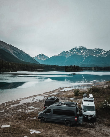 Scott's white van is parked alongside black and grey vans next to a lake, mountains are in the background.