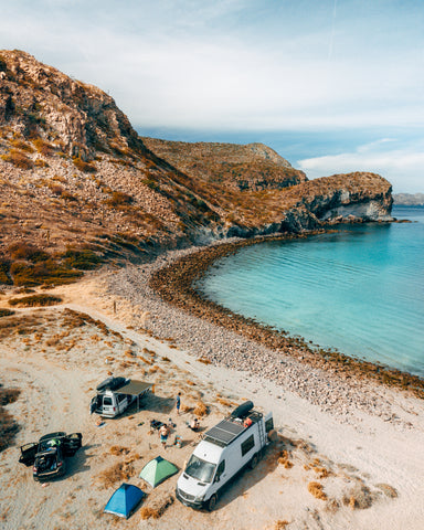 Scott's white Mercedes sprinter van is parked on a beach, in the background are clear blue waters and cliffs overlooking the campsite