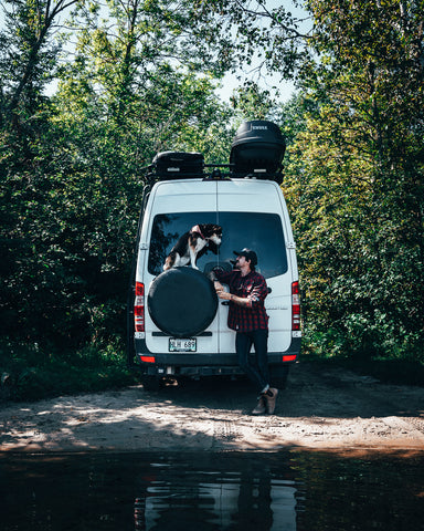 Scott stands behind his white Mercedes sprinter van in a forest with his dog, a Husky, who is sitting on top of the spare wheel.