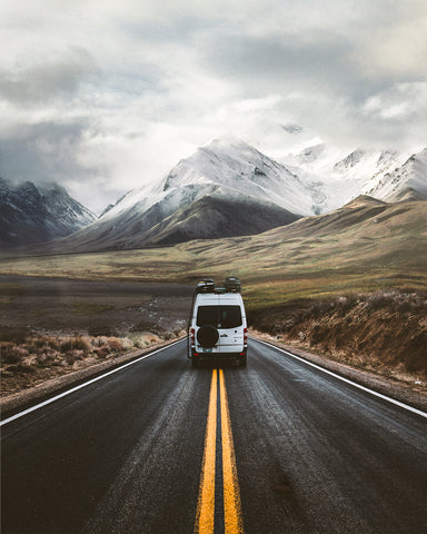 Scott's white van is driving along a road with rocky fields on either side, there's a mountain in the background