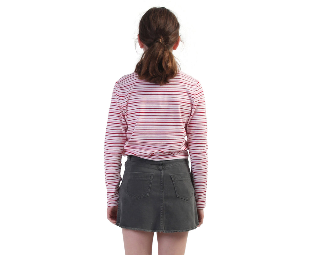 back view of teen girl wearing a pink red and white long sleeve tee