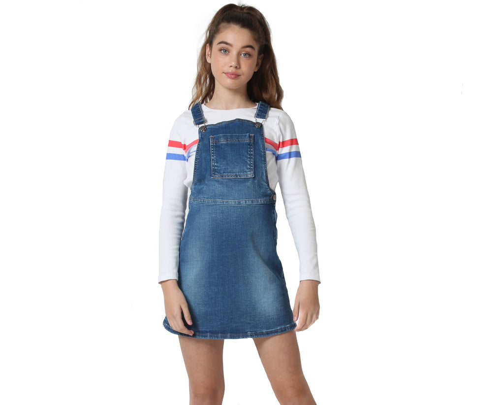 young girl wearing mid wash denim pinafore in blue