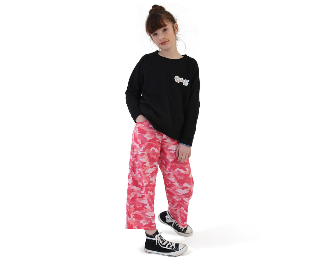teen girl wearing wide leg pants in pink camouflage print