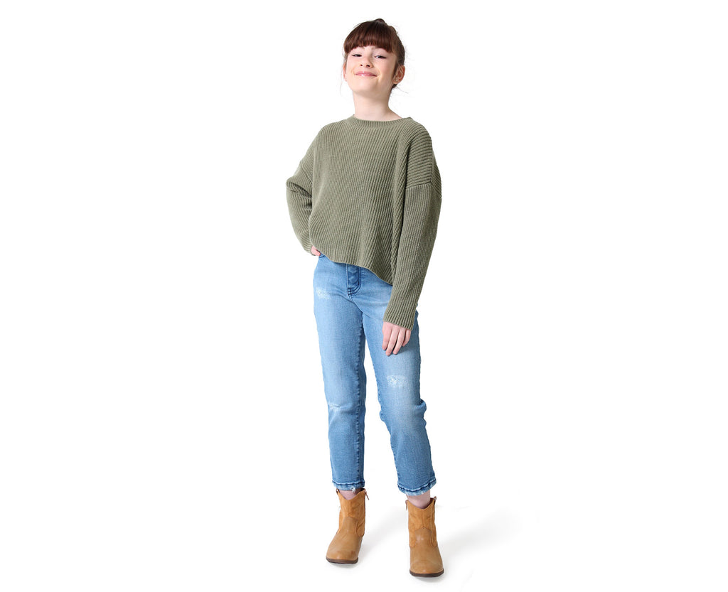 full body shot of young girl wearing a knitted khaki jumper