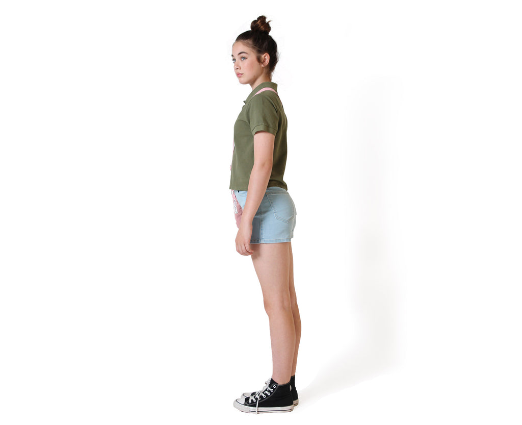 side view of girl wearing khaki polo top