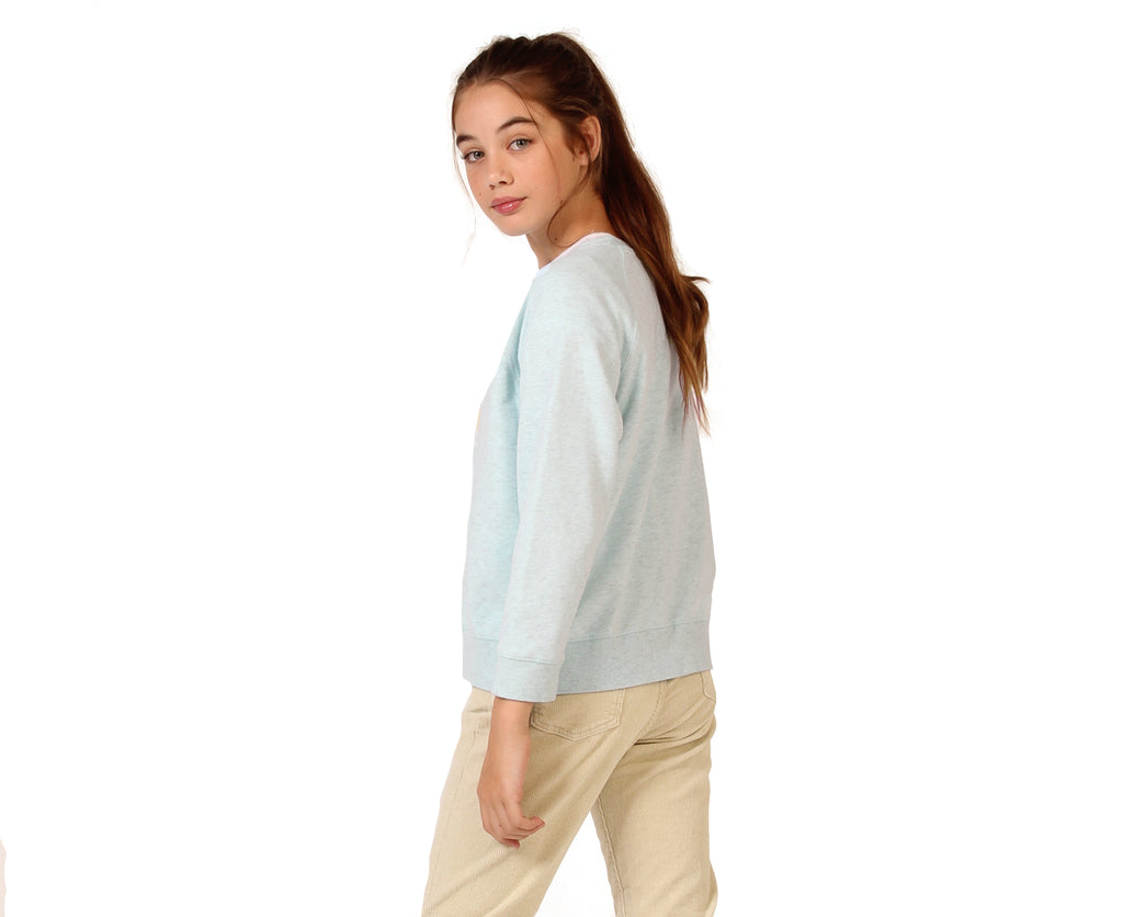 teenage girl wearing pale blue cotton sweater with front print