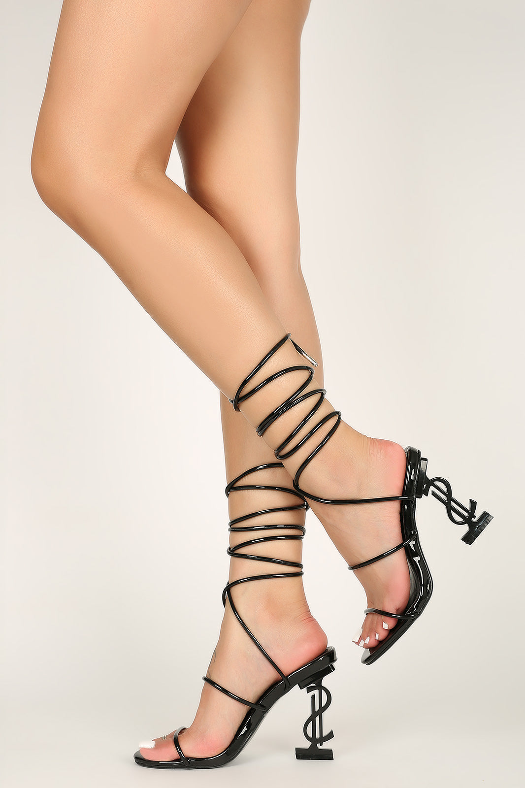 open toe silhouette, strappy vamp to a lace-up ankle closure, dollar sign