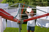 A woman hanging white clothes on her Sunshine Clothesline on a sunny day.